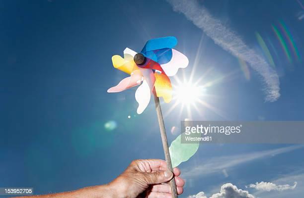 Germany, North Rhine Westphalia, Senior woman holding pinwheel against sky