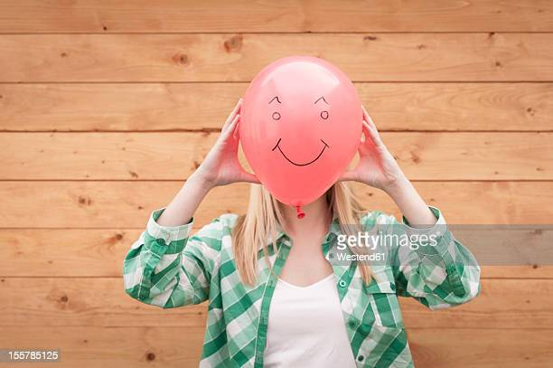 Germany, North Rhine Westphalia, Teenage girl covering face with smiley face balloon