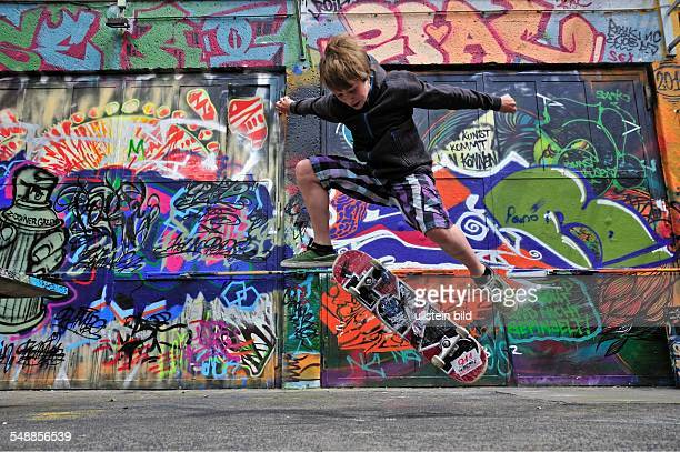Germany North RhineWestphalia Cologne boy with skateboard in front of a wall with graffity