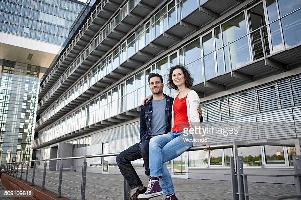 Germany, North Rhine-Westphalia, Cologne, couple sitting in front of facade at Rheinauhafen