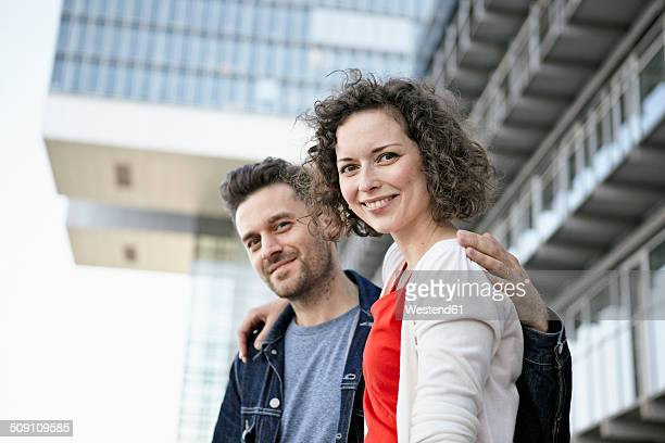 Germany, North Rhine-Westphalia, Cologne, portrait of couple in front of facade at Rheinauhafen