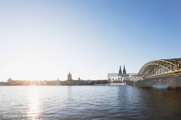germany, north rhine-westphalia, cologne, sun setting over rhine with hohenzollern bridge and cologne cathedral in background - ケルン市 ストックフォトと画像