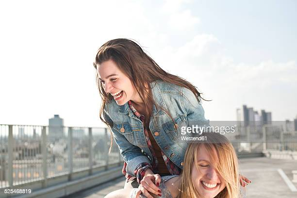 Germany, North Rhine-Westphalia, Cologne, two young women having fun on a parking level