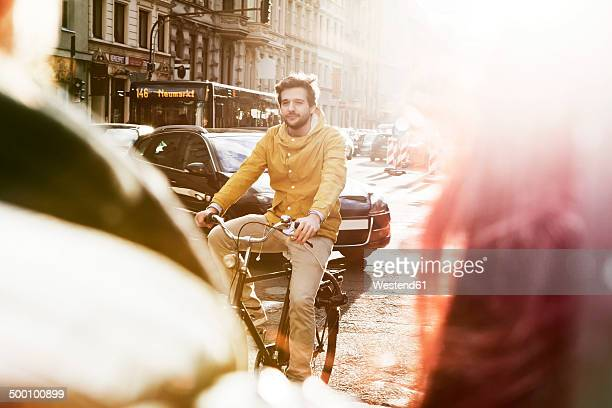 germany, north rhine-westphalia, cologne, young man riding bicycle - fahrrad stock-fotos und bilder