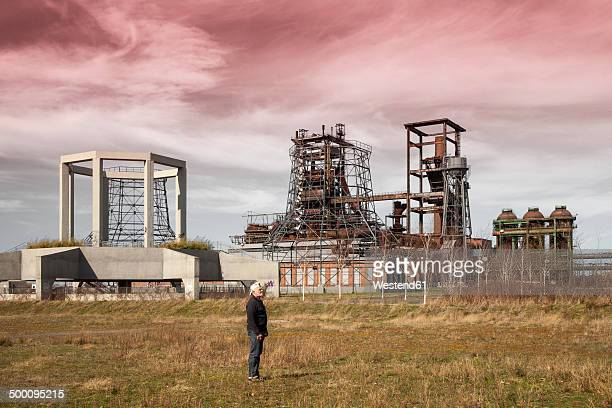 germany, north rhine-westphalia, dortmund-hoerde, senior standing on meadow and phoenix west in the background - ruhr stock pictures, royalty-free photos & images