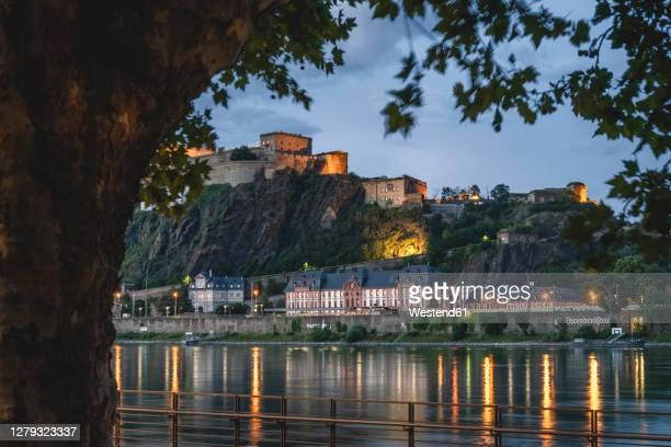 germany, north rhine-westphalia, koblenz, ehrenbreitstein fortress overlooking riverside buildings at dusk - コブレンツ ストックフォトと画像