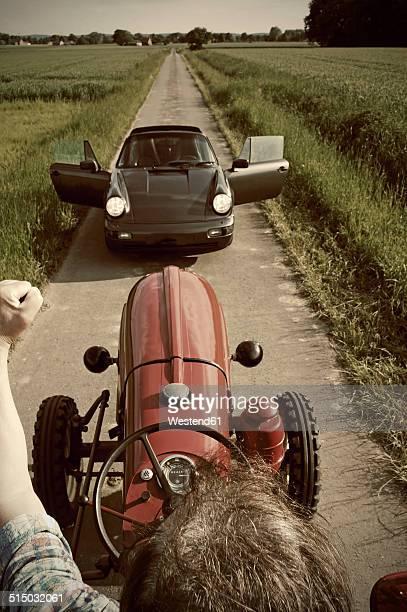 Germany, North Rhine-Westphalia, Minden, Porsche blocking the street, Man on old tractor