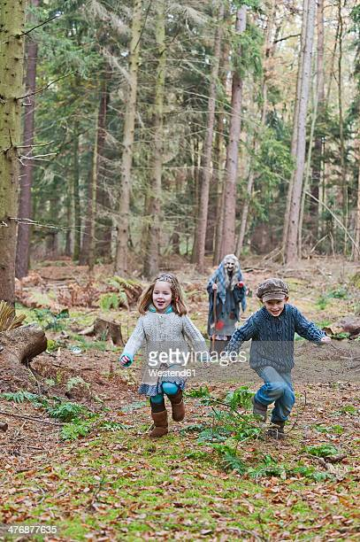 Germany, North Rhine-Westphalia, Moenchengladbach, Scene from fairy tale Hansel and Gretel, children running from witch