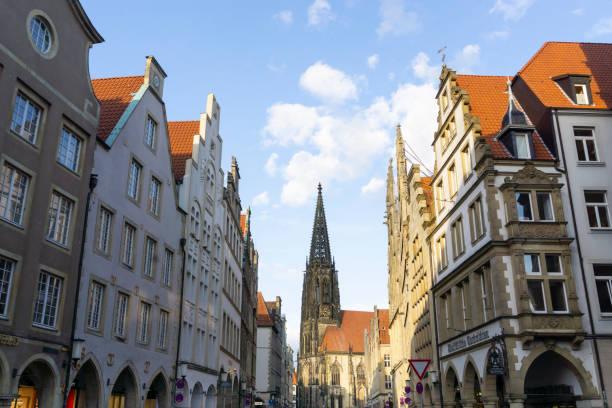 Germany, North Rhine-Westphalia, Munster, Tower of SaintLamberts Church between rows of residential buildings at Prinzipalmarkt square