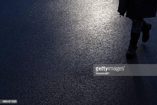 Germany, North Rhine-Westphalia, pedestrian walking on street at night