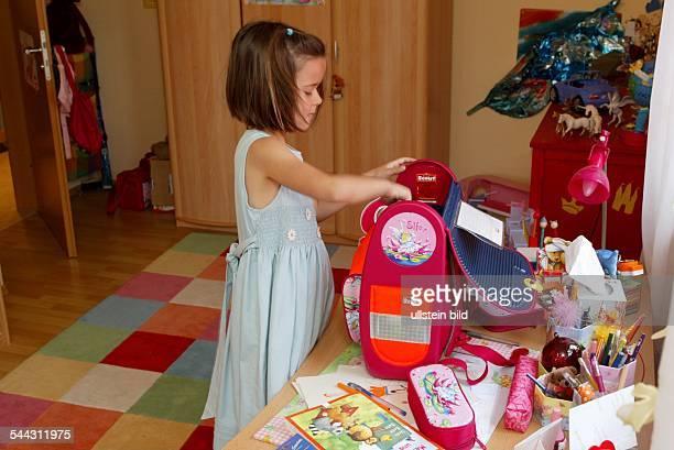 Germany North RhinWestphalia Troisdorf girl packing her satchel in children's room