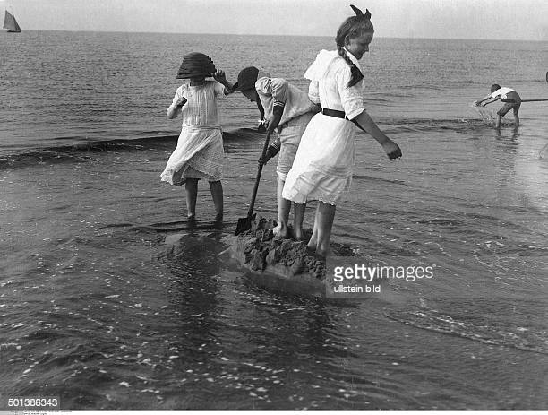 children playing on the beach in the 1910s