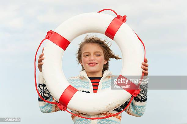 Germany, North Sea, St.Peter-Ording, Boy (8-9) holding life saver at beach, smiling, portrait