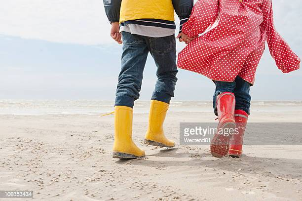 Germany, North Sea, St.Peter-Ording, Children (6-9) wearing boots and rain coats walking on beach, low section