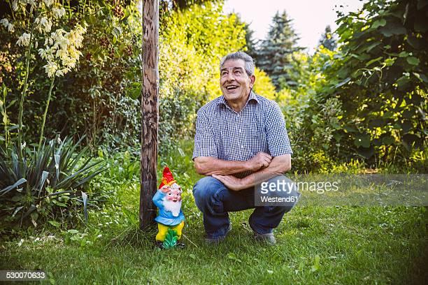 Germany, Northrhine Westphalia, Bornheim, Senior man crouching by gardengnome