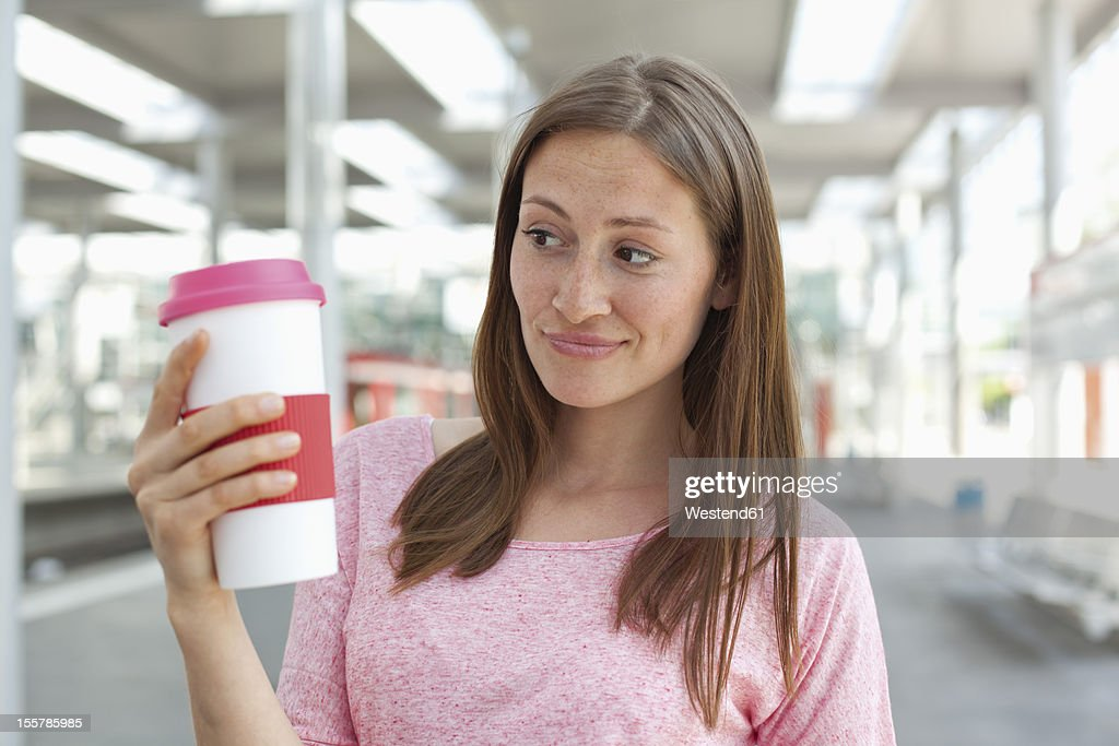 Germany, North-Rhine-westphalia, Duesseldorf, Young woman holding coffee cup : Stock Photo