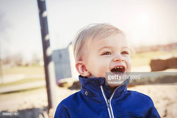 Germany, Oberhausen, toddler with open mouth on playground