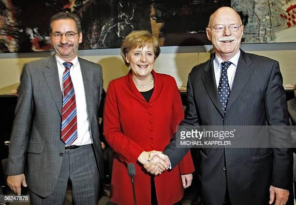 Outgoing German Defence Minister Peter Struck greets designated German Chancellor Angela Merkel as SPD chief Matthias Platzeck looks on after Struck...