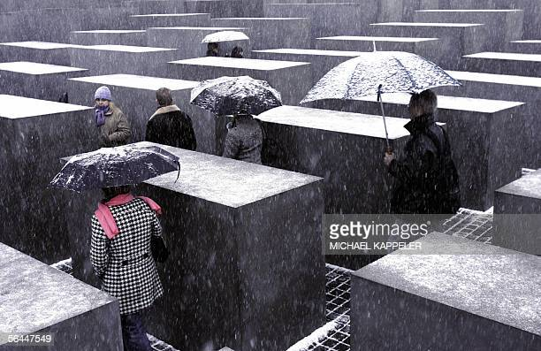People walk through the Memorial for the Murdered Jews of Europe under snow fall in Berlin after Germany experienced strong winds and snow fall 17...