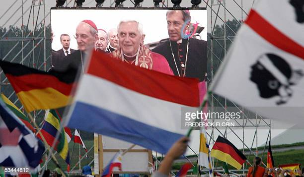 Pilgrims celebrate as they watch on a giant screen the arrival of Pope Benedict XVI accompagnied by Cologne's Archbishop Cardinal Joachim Meisner for...