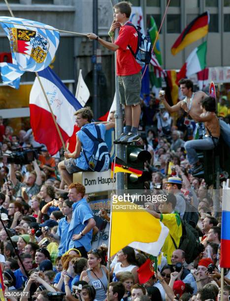 Pilgrims try to catch a glimpse of Pope Benedict XVI making his way through tens of thousands of World Youth Day pilgrims in his Popemobile in...