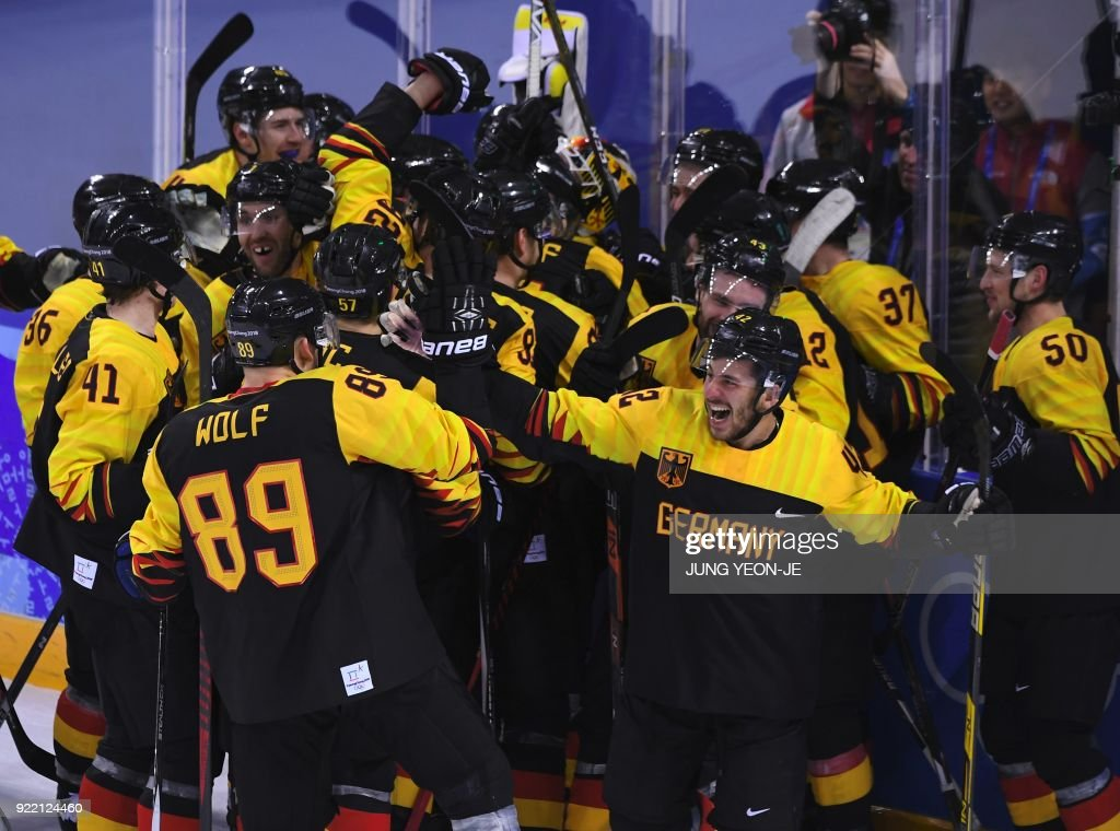 TOPSHOT - Germany players celebrate their victory after the men's quarter-final ice hockey match between Sweden and Germany during the Pyeongchang 2018 Winter Olympic Games at the Kwandong Hockey Centre in Gangneung on February 21, 2018. / AFP PHOTO / Jung Yeon-je