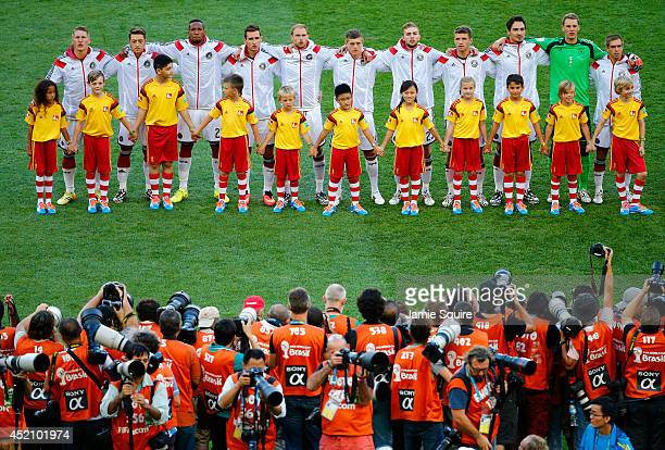Germany players line up on the pitch for the National Anthem prior to the 2014 FIFA World Cup Brazil Final match between Germany and Argentina at...