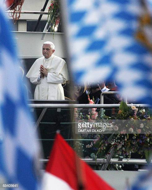 Pope Benedict XVI cheers pilgrims aboard the RheinEnergie as Cologne's Archbishop Joachim Meisner and Mainz' cardinal Karl Lehmann look on as he...