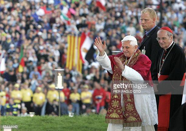 Pope Benedict XVI flanked by the archbishop of Cologne Cardinal Joachim Meisner waves to faithful and pilgrims as he arrives at the Marienfeld a...