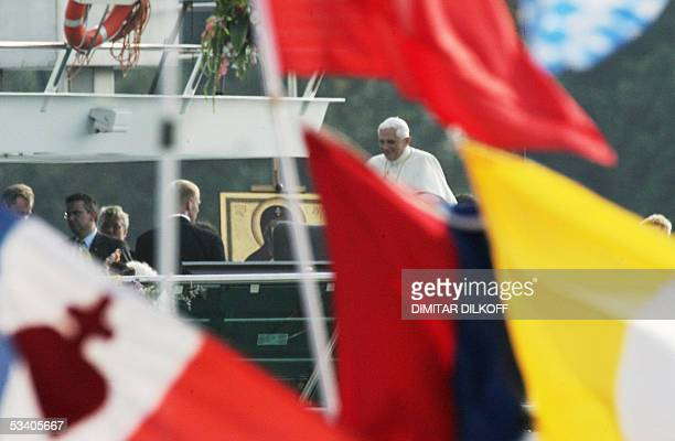 Pope Benedict XVI is seen behind flags as he cheers pilgrims aboard the RheinEnergie as Cologne's Archbishop Joachim Meisner and Mainz' cardinal Karl...