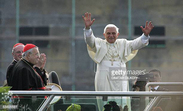 Pope Benedict XVI waves to pilgrims aboard the RheinEnergie as Cologne's Archbishop Joachim Meisner and Mainz' cardinal Karl Lehmann look on as he...