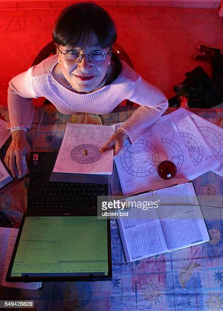 Portrait of a astrologer working with her notebook and several celestrial charts