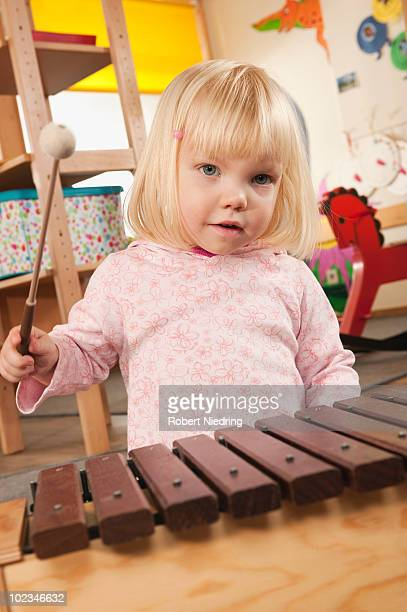 Germany, Girl (2-3) playing xylophone, portrait, close-up