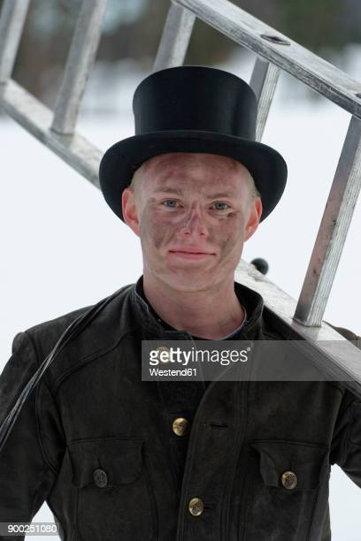 Germany, portrait of chimney sweep with ladder wearing top hat