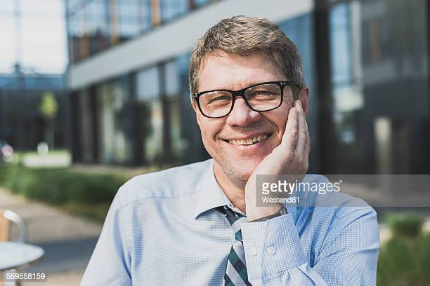 Germany, Portrait of mature businessman, hand on chin, smiling