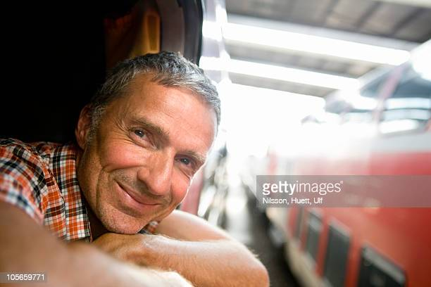 Germany, portrait of mature man looking through window