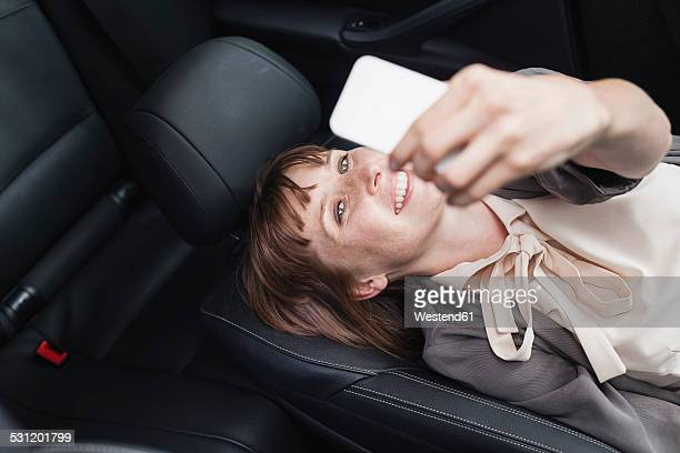 Germany, portrait of smiling businesswoman taking in selfie in her car with smartphone