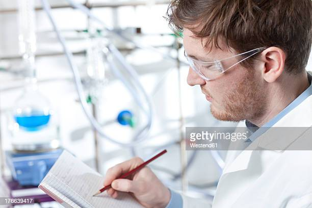 Germany, Portrait of young scientist making notes in booklet, smiling
