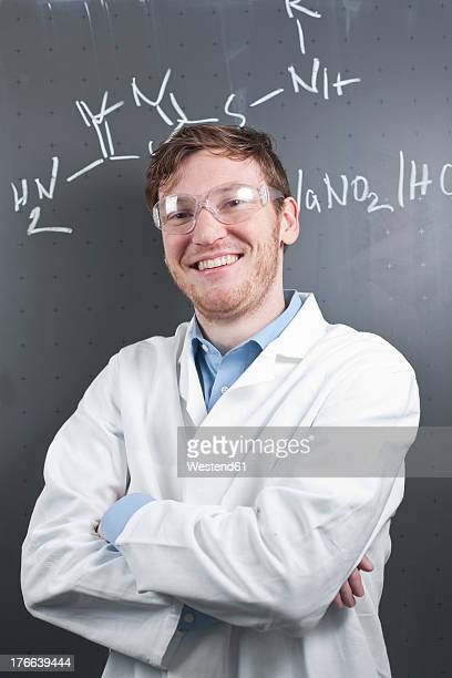 Germany, Portrait of young scientist standing in front of chemical equation on chalk board, smiling