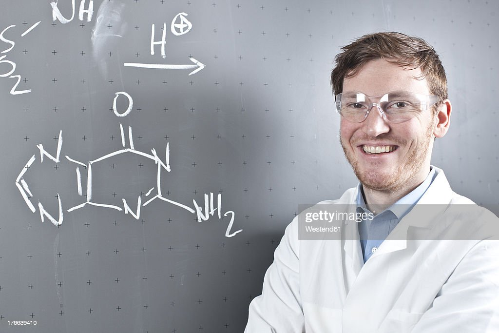 Germany, Portrait of young scientist standing next to chemical equation on chalk board, smiling : Stock Photo