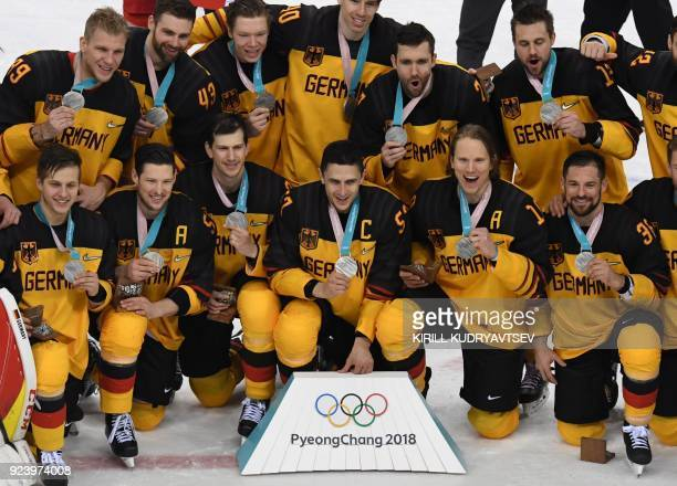 Germany pose with their silver medals after the medal ceremony in the men's gold medal ice hockey match between the Olympic Athletes from Russia and...