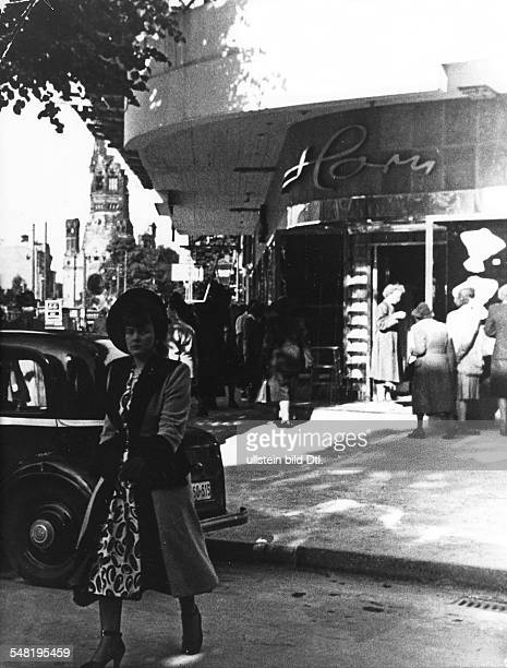 Germany Post War Years in Berlin 194549 Street scene by a ladies' fashion shop on the Kurfuerstendamm Road| in the background the ruin of the Emperor...