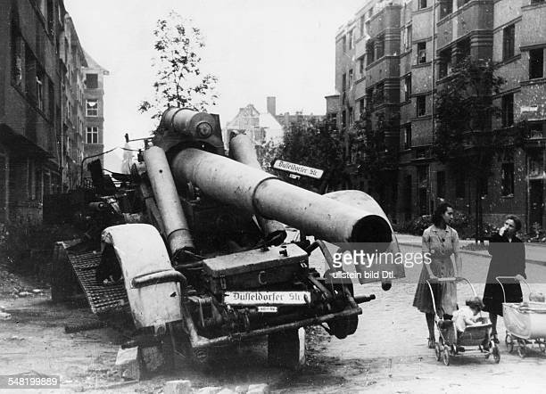 Germany Post War Years in Berlin 194549 Two mothers pushing their buggies past a destroyed flak in Berlin 1945