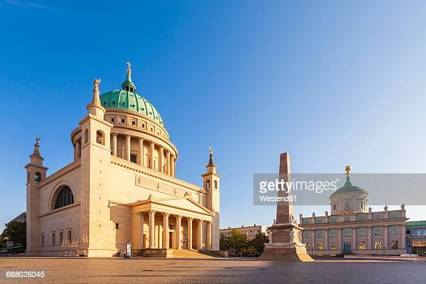 Germany, Potsdam, view to St. Nicholas church, obelisk and old city hall at old market in the evening