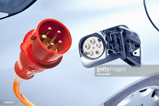 Germany, Power cord with electric car, close up