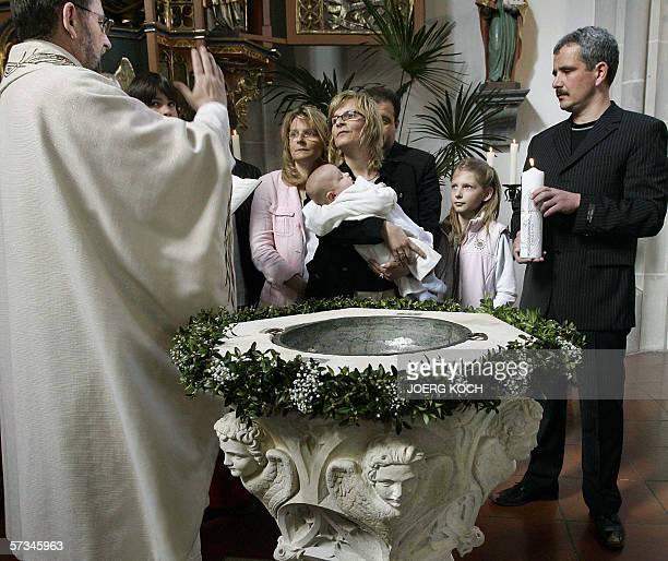 Priest Josef Kaiser christens little Julian Lorenz Benedikt Reissl as the boy's parents Annette and Lorenz Reissl and godparent Silvia Flachner look...