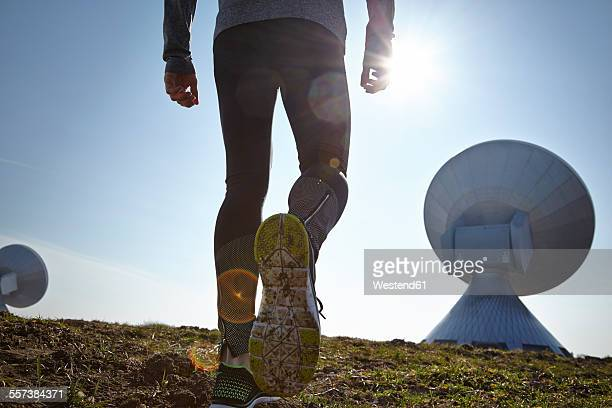 Germany, Raisting, back view of young jogger at ground station
