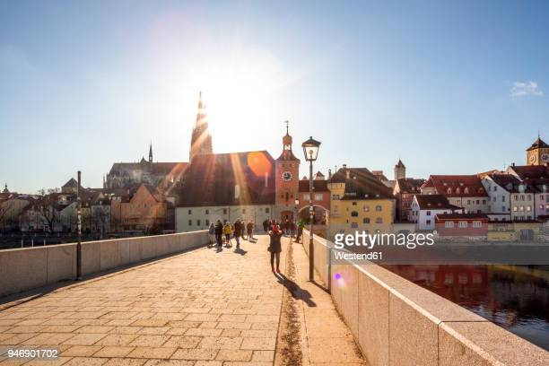 germany, regensburg, view to cathedral at the old town with steinerne bruecke in the foreground - regensburg stock photos and pictures