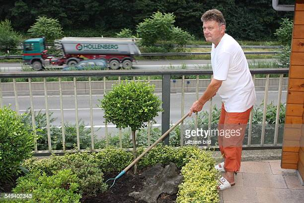 """Germany, Reportage """"Living at the highway 40"""". Essen. Man working in his garden next to the expressway"""