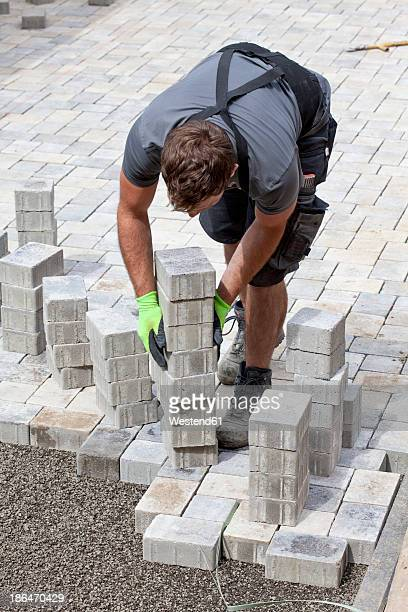 germany, rhineland palatinate, young man assembling paving stones - paving stone stock pictures, royalty-free photos & images